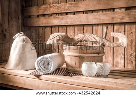 Sauna. Bathroom Accessories: bucket, spoon carving, hat, rolled in a roll towel and a vase of scented candles. - stock photo