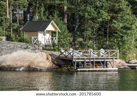 Sauna building and wooden patio by the lake in relaxing surrounding - stock photo