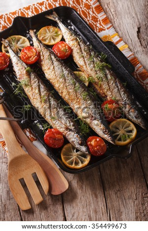 saury grilled with lemon and tomato on a grill pan on a table. Vertical