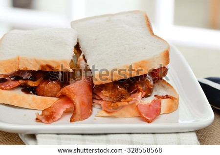 Sausage and bacon sarnie with brown sauce on white bread. - stock photo