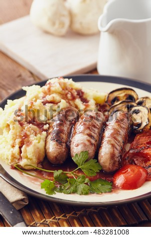Sausage and mush dish with grilled mushrooms and tomatoes