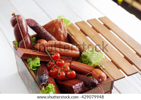 Sausage assortment in wooden box. Box with different kinds of sausages decorated with cherry tomato on white wooden background. - stock photo