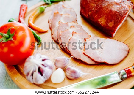 Sausage, cutting board and knife arranged on a wooden table for a snack in the countryside.