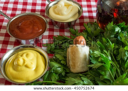 Sausage in the dough ( Mini hot dog homemade ) on parsley leaves with mustard, mayonnaise, ketchup and cola on a plaid background - stock photo