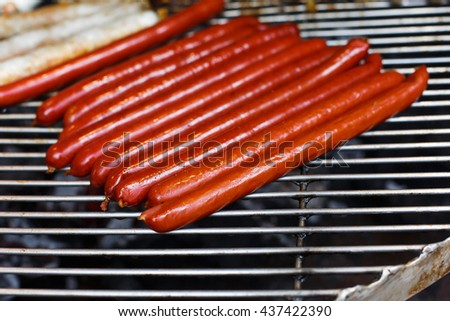 Sausage party. Barbecue large grill outdoors. Cookout bbq food. Big roasted pork and beef german sausages, white polish kielbasa. Meat grilled snack. Street food, fast food. Tasty appetizer, sausages. - stock photo