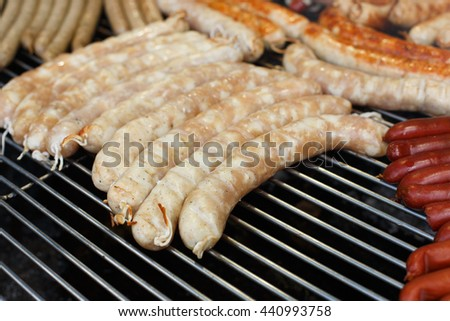 Sausage party. Barbecue large grill outdoors. Cookout bbq food. Big roasted pork german bratwurst, white polish kielbasa. Meat meal. Street food, fast food. Tasty snack - stock photo