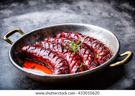 Sausage. Roasted chorizo sausage. Roasted spicy sausage chorizo home hotel or restaurant with beer vine brandy cognac whiskey. Still life. Toned photo. - stock photo