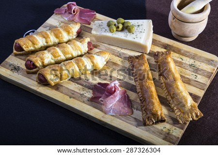 Sausage rolls and stuffed puff pastry bags on a plate