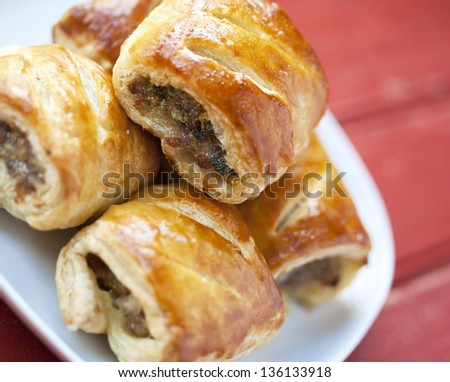 Sausage rolls on a plate on a wooden table - stock photo