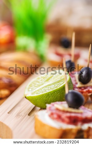 Sausage sandwiches, cheese and olives on toothpick, wooden table in background. - stock photo