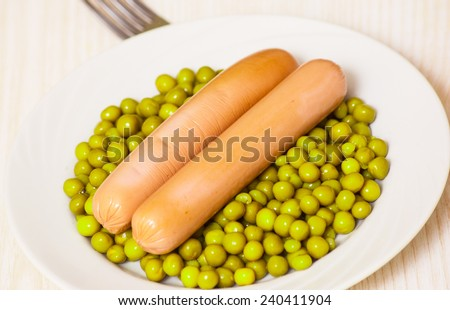 sausage with green peas on a white plate - stock photo