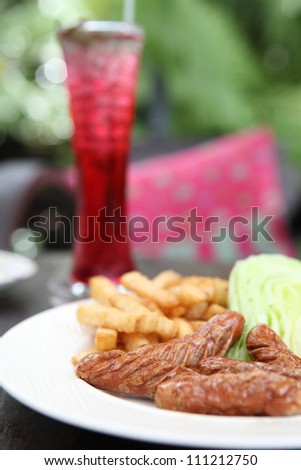 Sausage with potato on wood background - stock photo