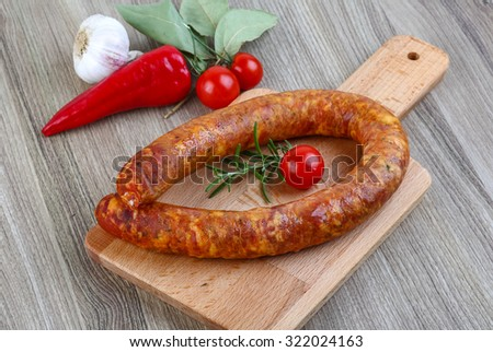 Sausage with rosemary and tomato on the wood ready for cooking