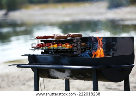 Sausages and vegetables on barbecue grill, outdoors