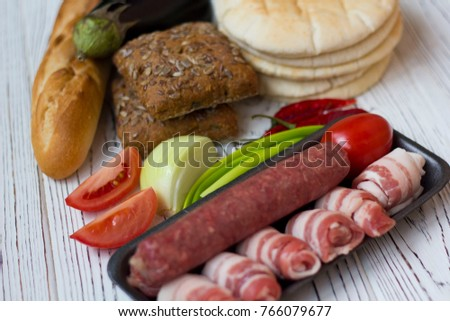 sausages, bacon, vegetables and bread on white wooden table