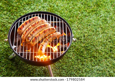 Sausages grilling over the hot glowing coals in a portable barbecue standing on a green lawn with copyspace during a picnic or summer camping trip - stock photo