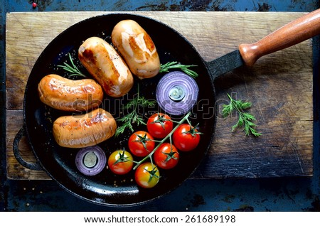 Sausages in a cast iron pan, top view - stock photo