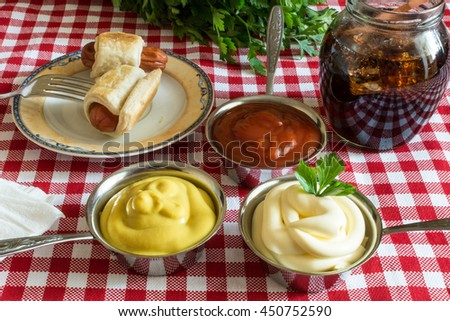 Sausages in dough (Mini hot dog homemade) with ketchup, mayonnaise and parsley on the plate and cola in a glass jar - stock photo