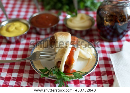 Sausages in dough (Mini hot dog homemade) with ketchup, mayonnaise and parsley on the plate and and cola in a glass jar - stock photo
