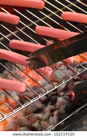 Sausages on barbecue with tongs with glowing charcoal below (Selective Focus, Focus on the end of the tongs and the lower end of the sausage they touch) - stock photo
