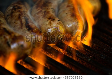 sausages on the barbecue, close up with smoke and flames
