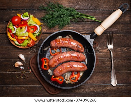 Sausages on the grill pan on the wooden background. Top view. Frying pan with fried sausage and vegetables on a rustic wooden table.  - stock photo
