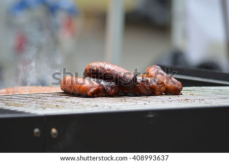 sausages on the grill with smoke on blurred background