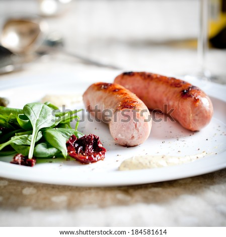 Sausages roasted on a grill with spinach and sun dried tomatoes salad on a white plate on a served table - stock photo