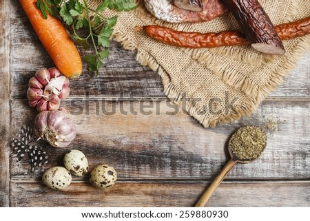 Sausages, spices and garlic on wooden table - stock photo