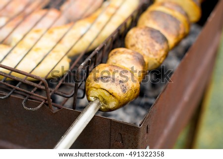 sausages with potatoes on the grill, baked potato, brazier