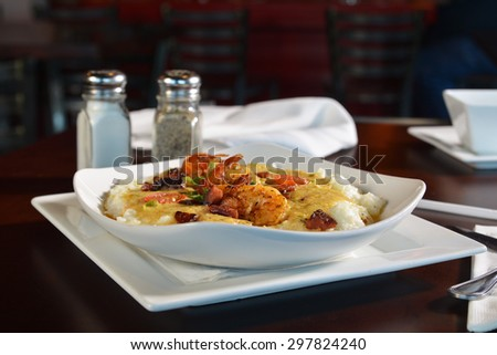 Sauteed shrimp prawns with creole butter sauce, peppers, and vegetable medley on creamy grits - stock photo