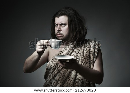Savage man in skin of beast drink tea or coffee - stock photo