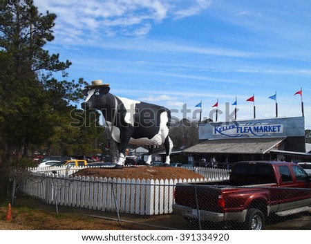 SAVANNAH, GEORGIA - FEBRUARY 20, 2016: A giant cow sculpture, formerly belonging to a Savannah area dairy, decades ago, now stands in front of Keller's Flea Market, on the outskirts of Savannah, GA.  - stock photo