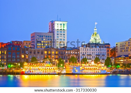 Savannah Georgia USA, skyline of historic downtown at sunset with illuminated buildings and steam boats
