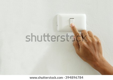 save energy concept,closeup of finger touching to electric switch off with copy space - stock photo