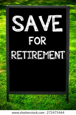 SAVE FOR RETIREMENT  message on sidewalk blackboard sign against green grass background. Copy Space available. Concept image - stock photo