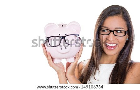 Save money on glasses eyewear.A portrait of a young woman happy and excited over savings on buying eyewear glasses. Piggybank and woman wearing glasses isolated on white background. - stock photo