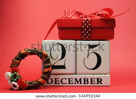 Save the Date for Christmas day with this white wooden blocks calendar for December 25, with a festive red present gift and Christmas wreath against a red background. - stock photo