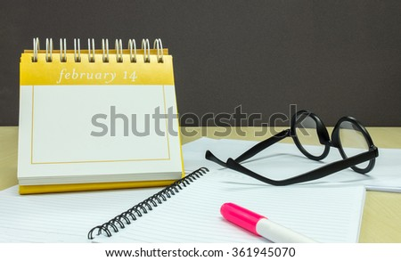 Save The Date for Your Love on Valentine's Day, Calendar of February 14 with Pink Highlight Pen, Notebook and Glasses on Wooden Office Desk - stock photo