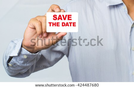 SAVE THE DATE message on the card shown by a man,Human hands holding blank advertising card isolated on white background,asian business man show white card in hand,selective focus,vintage color. - stock photo