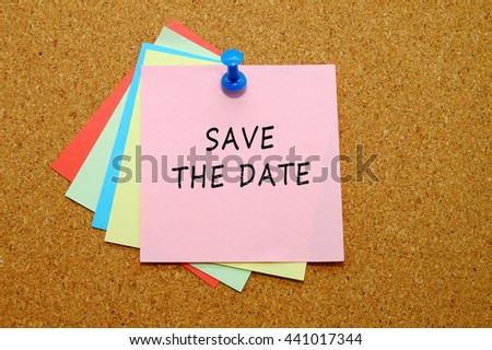 Save the date written on color sticker notes over cork board background. - stock photo