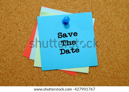 Save The Date written on colored sticker notes over cork board background.