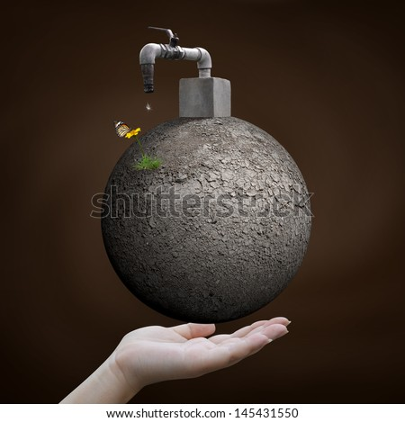 save water concept, hand holding arid world with faucet - stock photo