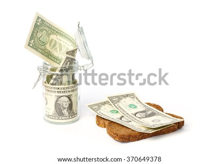 Saved dollars in a storage jar and on a slice of bread - stock photo