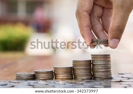 Saving and Business concept, hand putting coins to coin stack growing graph