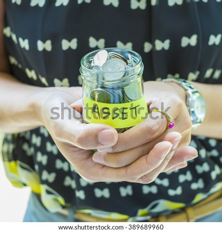 Saving and investment concept image. Woman  holding money jar with ASSET label. Representing saving for invest in asset. - stock photo
