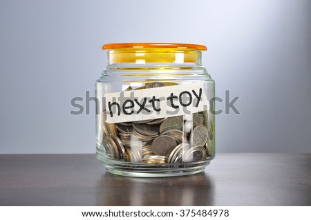 Saving concept of coins in the glass jar for next toy  purpose.
