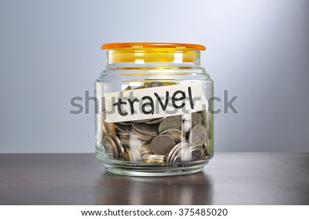 Saving concept of coins in the glass jar for travel  purpose.