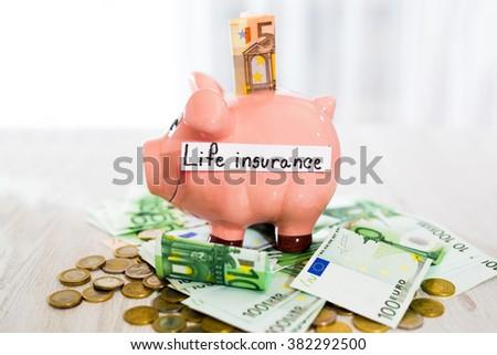 Saving concept. Piggy bank with an inscription life insurance. Selective focus - stock photo