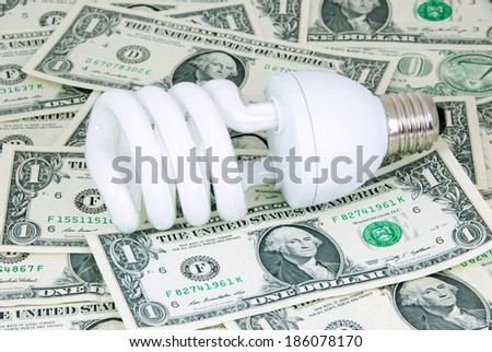 Saving energy bulb on money for the saving energy expense concept. - stock photo